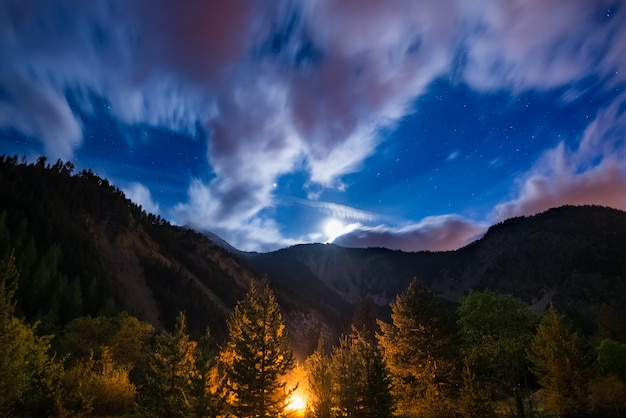 The starry sky with blurred motion clouds and bright moonlight, captured from larch tree woodland, glowing by burning fire. expansive night landscape in the european alps. adventure into the wild.