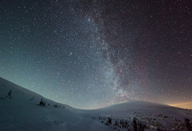 The starry sky with pink haze is located above the winter ski resort