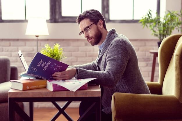 별과 운명 점성술을 배우면서 시작에 대한 백과 사전을 공부하는 진지한 착한 남자