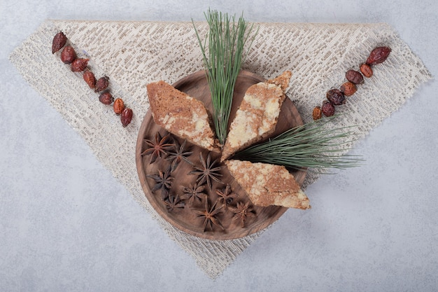 Anice stellato con tre torte dolci sul piatto di legno.