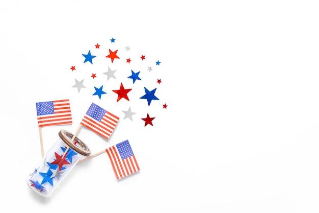 星紙吹雪、アメリカの国旗は、白い背景で隔離のガラスを飛ぶ。テキストのためのスペース。 7月4日。アメリカの独立記念日の装飾。テキストのためのスペース