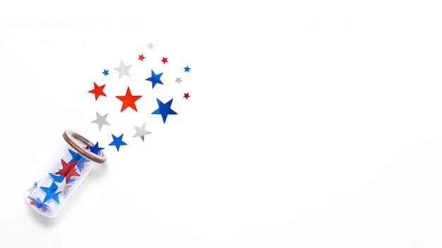 アメリカの国旗の色の星紙吹雪が白い背景で隔離のガラスを飛ぶ。テキストのためのスペース。 7月4日。アメリカの独立記念日の装飾。