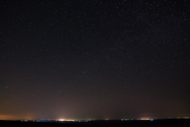 Stars in the dark night sky with city lights on the horizon