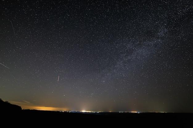 Звезды в темном ночном небе с огнями города на горизонте.