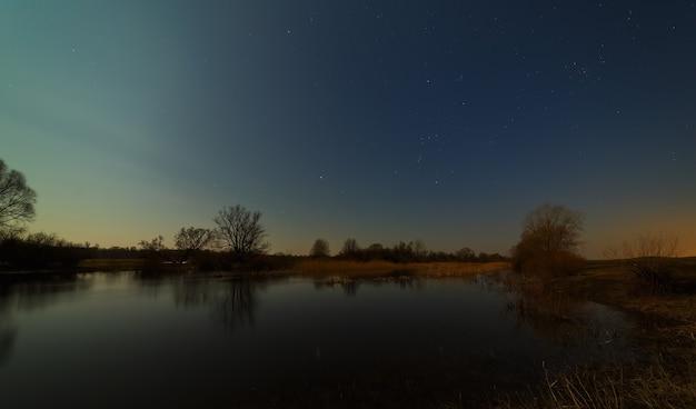 Звезды в ночном небе над рекой. ранняя весна в средней полосе россии.