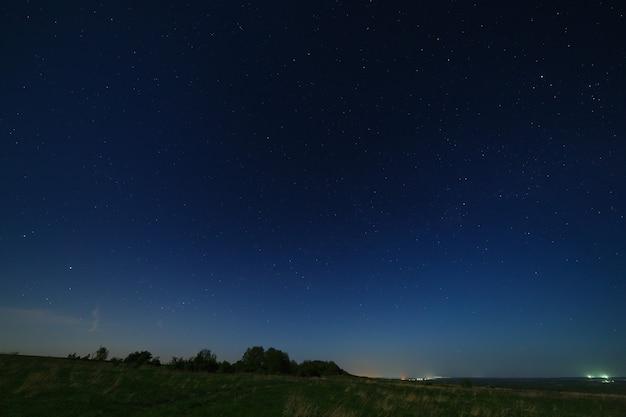 地平線に街の明かりが灯る夜空の星。風景は月明かりで撮影されています。