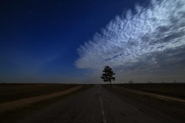Звезды в ночном небе с облаками над дорогой. пейзаж сфотографирован при лунном свете.