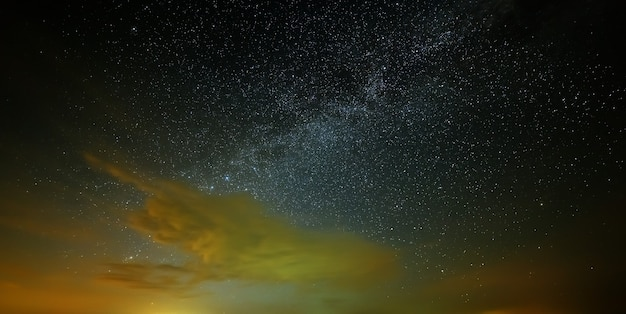 The stars of the milky way with clouds in the night sky