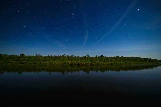 The stars in the night sky are reflected in the river. . the landscape is photographed by moonlight.