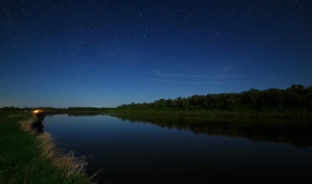 The stars in the night sky are reflected in the river. the landscape is photographed by moonlight.