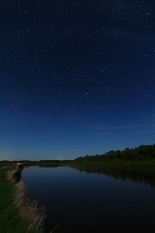 The stars in the night sky are reflected in the river