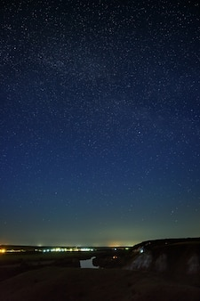 Stars in the night sky over the river valley and city. the cosmic space