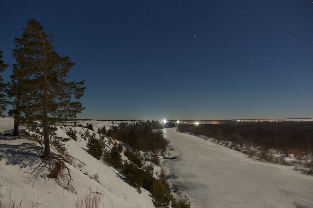 Stars in the night sky. winter landscape with a frozen river photographed under the full moon.