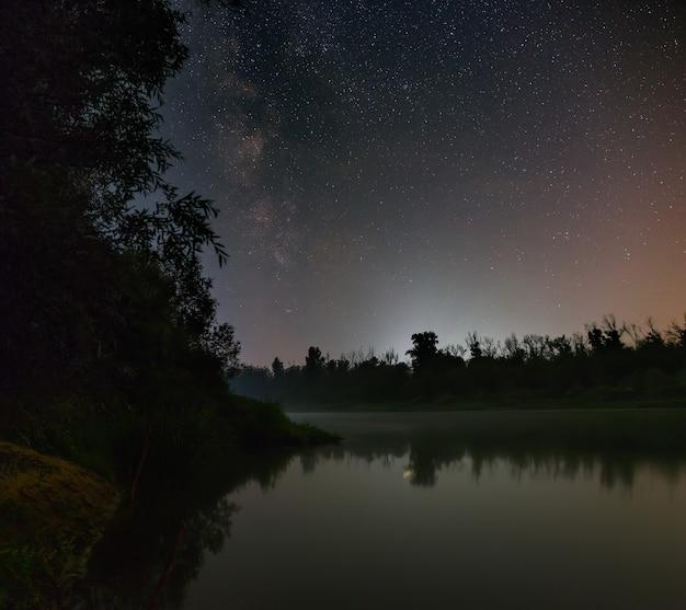 Звезды галактики млечный путь в ночном небе над рекой. снято с длинной выдержкой.