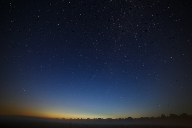 Звезды галактики млечный путь в ночном небе. пространство на фоне утренней зари.