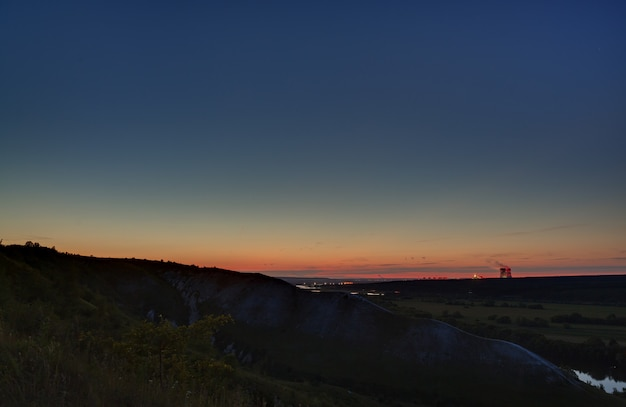 Stars of outer space in the night sky over the river valley. landscape in the twilight on long exposure.