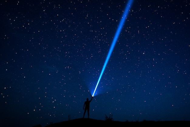 Stars in the sky. the traveler looks at the starry sky. night sky with stars and silhouette of a man with raised-up arms. the man with the lantern. a strong beam of light. powerful flashlight
