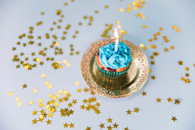 Stars spread around the illuminated candle over the cupcake on golden plate