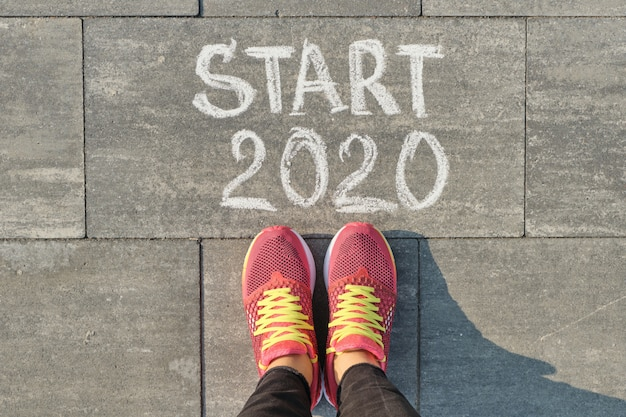 Start 2020, text on gray sidewalk with woman legs in sneakers, top view
