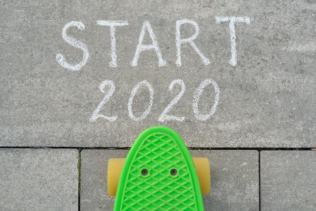 Start 2020 written in chalk on gray sidewalk, skateboard before the text.