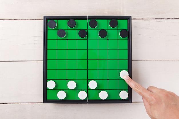 Начните игру с шашкой на зеленой доске сверху сверху на деревянный стол.