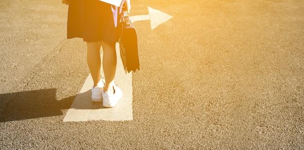 スタートラインの開始アイデアで、アスファルト道路の背景に子の足と矢印を開始します。制服ウォーキングシューズの子供たちのビューの上のselfie。子どもたちの学校は前進し、新たなスタートと成功を収めています。
