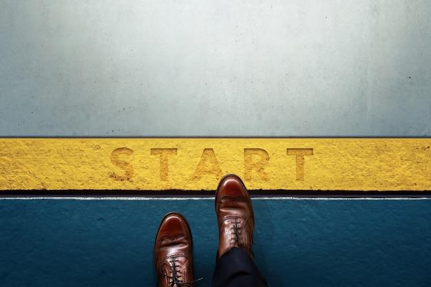 コンセプトを開始します。スタートラインへのビジネスマンのステップの上面図。ビジネスチャレンジまたは何か新しいことをする Premium写真