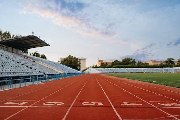 Start line for running on stadium, nobody, front view. empty treadmill with numbers, injury-proof coating, jogging surface on sport arena