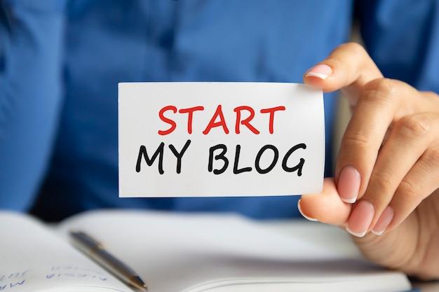 내 블로그 시작은 여성의 손에 있는 흰색 명함에 쓰여 있습니다. 파란색 배경입니다. 비즈니스 및 광고 개념
