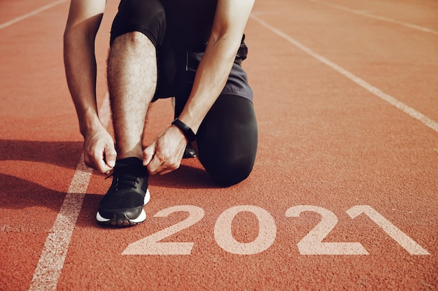 Start to new year  plansstart of man running on running courtwith sunset lightgoal of success concept