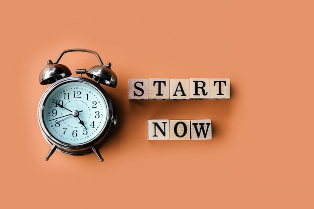 Start now concept with text and alarm clock on brown background