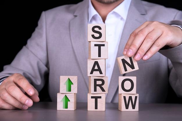 今すぐ始めましょう、単語、テキスト、木製の立方体、男性の背景にある立方体、灰色のスーツを着たビジネスマンに書かれています。