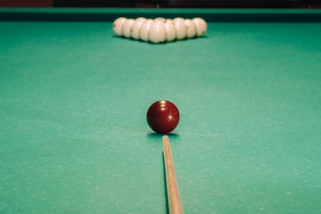 緑のテーブルでビリヤードのゲームを開始します。ボールはテーブルの上に三角形に配置されています。 Premium写真