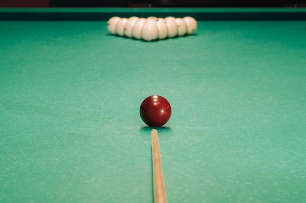 緑のテーブルでビリヤードのゲームを開始します。ボールはテーブルの上に三角形に配置されています。