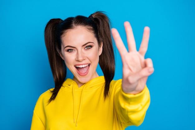 세 번째부터 시작합니다. 예쁜 여성의 두 꼬리 사진이 세 손가락을 보여주는 팔을 들고 밝은 파란색 배경에 격리된 캐주얼한 노란색 후드티 풀오버를 입고 있습니다.