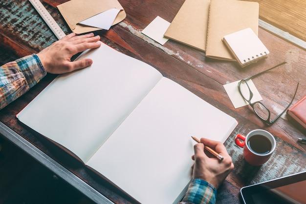 Начните планировать сегодня. крупным планом вид сверху изображение человека, пишущего в блокноте с копией пространства, сидя за деревенским деревянным столом