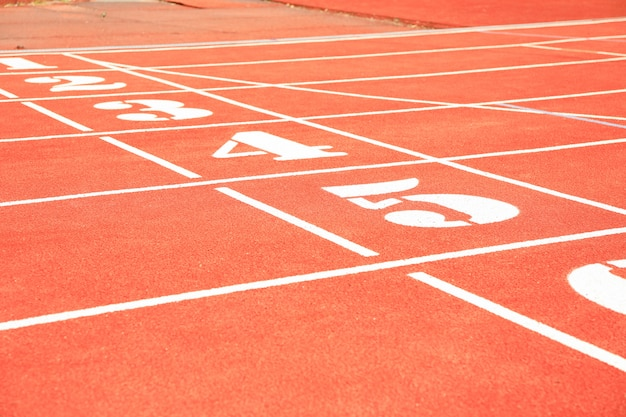 Start of red athletic track with numbers. sport concept