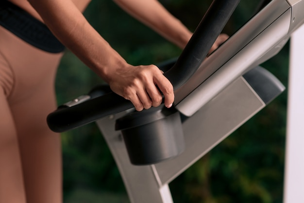 Start running. a close-up photo of a woman in sportswear holding the handle of an exercise bike in the gym with her hands.