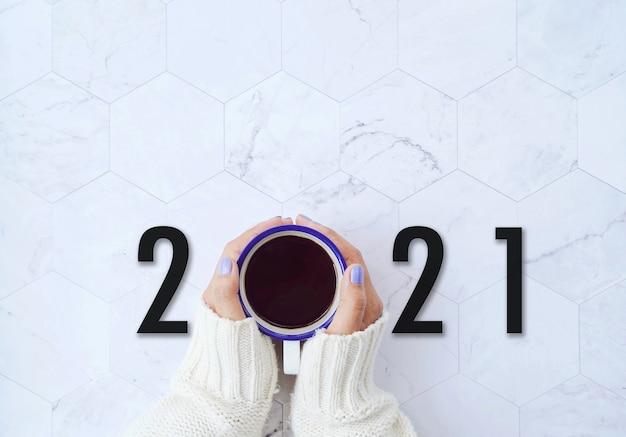 新年2021コンセプト、白い大理石の背景に熱いコーヒーを持っている女性の手の上面図、目標と動機付けの計画を開始します。