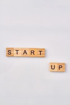 Запуск как бизнес-концепция. начало нового дела. деревянные блоки алфавита изолированные на белой предпосылке.