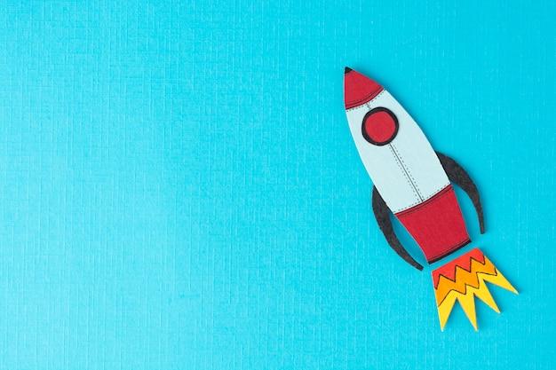 事業を開始します。収入、給料を増やしたり増やしたりします。カラフルな青色の背景に描かれたロケット。 copyspace。