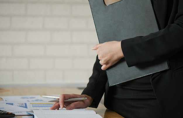 Start up business concepts, new generation managers hold files on hand and checking work data from graphs.