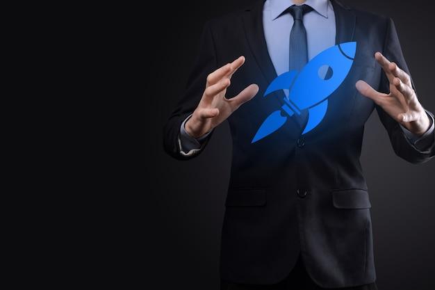抽象的なデジタルロケットアイコンを保持しているビジネスマンとの概念を起動しますロケットが起動し、飛んで急上昇します