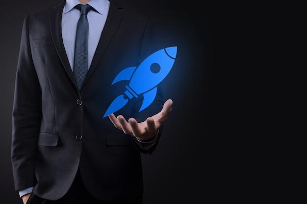 抽象的なデジタルロケットアイコンを保持しているビジネスマンとのコンセプトを開始しますロケットが打ち上げられ、飛んでいます。