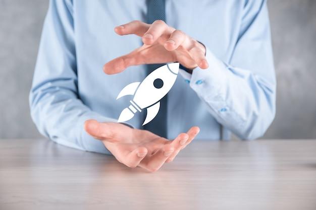 Запуск концепции с бизнесменом, держащим абстрактный цифровой значок ракеты. ракета запускает и парит в воздухе.