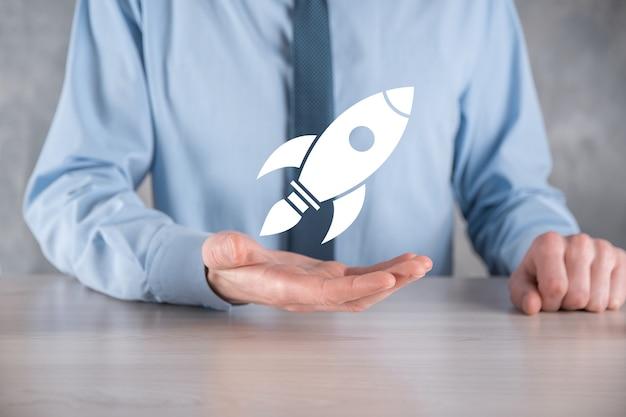 Запуск концепции с бизнесменом, держащим абстрактный цифровой значок ракеты. ракета запускает и взлетает.