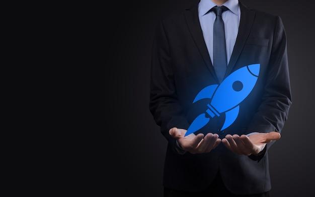 抽象的なデジタルロケットアイコンを保持しているビジネスマンとの概念を開始しますロケットが打ち上げられ、飛んで急上昇します