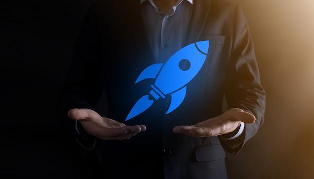 抽象的なデジタルロケットアイコンを保持しているビジネスマンとのコンセプトを開始しますロケットが打ち上げられ、飛んで急上昇します。