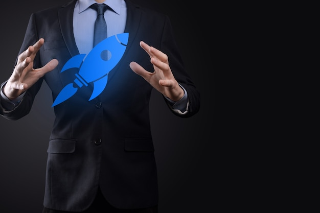Start up concept with businessman holding abstract digital rocket icon rocket is launching and soar flying