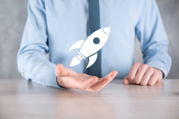 Start up concept with businessman holding abstract digital rocket icon rocket is launching and soar flying.